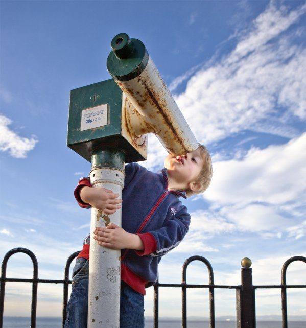Boy looking through wrong end of telescope